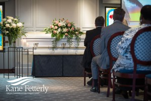 Couple viewing recording of funeral ceremony on their laptop