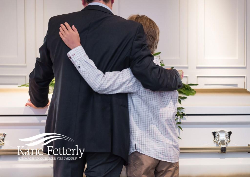Père qui console son fils pendant des funéraiilles