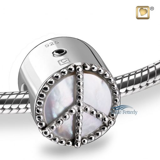 Bead with peace motif on a mother of pearl background.