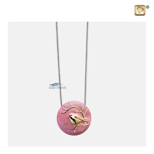 Pendentif cinéraire rond, motif oiseau doré sur fond rose émaillé.
