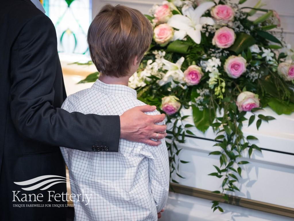 Père qui console son jeun fils pendant des funérailles