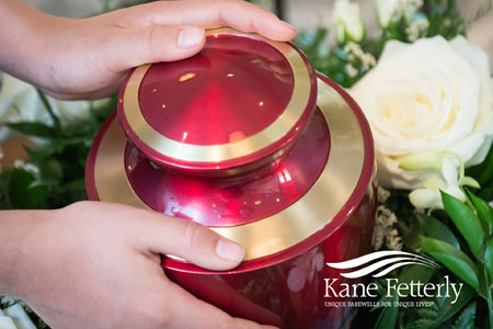 Hands of a woman gently holding funeral urn
